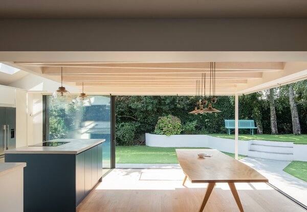 The zig-zag ceiling adds a sense of playfulness and maximizes the visual volume of the open-concept kitchen and dining area. Combined with the oversized sliding doors, the space feels incredibly open and airy.