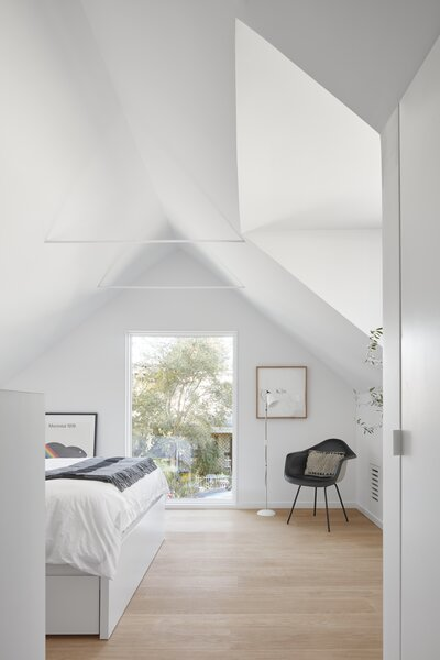 The only furniture in the bedroom is the bed and a side chair. Light pours in through the angled sky-light and oversized window to the street.