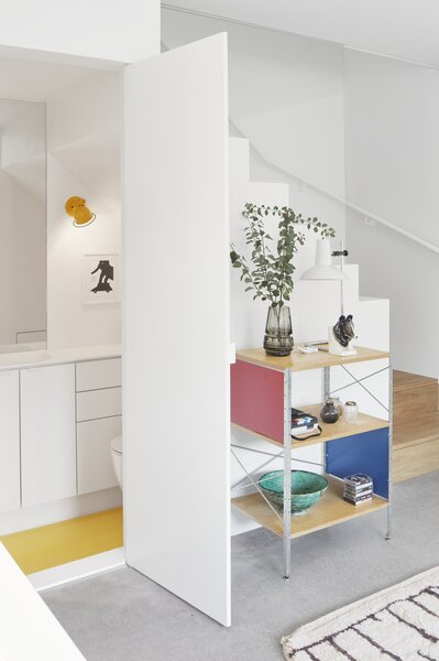 A yellow epoxy floor matches the sconce in the tiny bathroom that sits under the staircase.