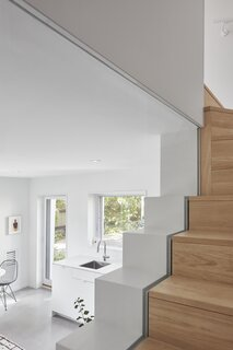A slight extension of drywall out from the stair treads helps create enough space underneath to squeeze a bathroom.