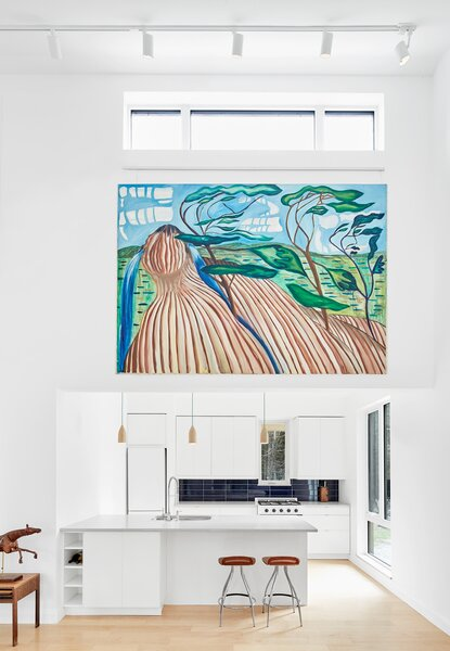 """The white walls act as the perfect gallery space for the couple's artworks. """"The walls are a bit of an odd proportion because the ceiling is so tall, but I think there's kind of a beauty in that oddness,"""" says Lolley."""