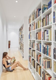 """The couple are avid readers; a hallway of shelving is now home to their ample book collection. """"As we walk by, we catch a glimpse of something we haven't read in 30 years… or never have read at all,"""" says Donna."""