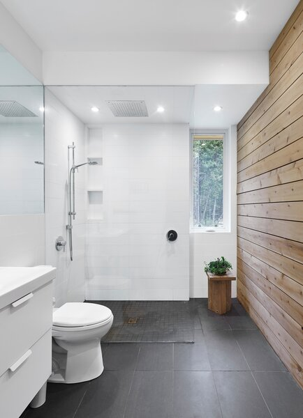 The bathroom floor is grey porcelain, equipped with radiant heating. A cedar wall adds a different kind of warmth to the space.