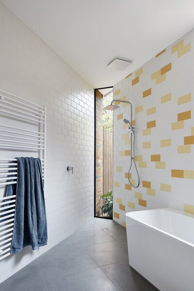 The subway tiles in the bathroom echo the pattern of the bricks elsewhere in the house. Strategically placed windows let the daylight flow in, even during bath time.