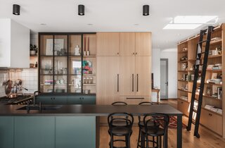 A cantilevered peninsula offers a smart, space-saving solution for the 900-square-foot layout: It offers ample space for food preparation and also acts as a dining area.