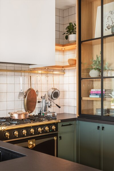 In the kitchen, mullioned glass cabinets showcase Isabella's tableware and treasures, while a brass pot rail makes it easy to grab her cooking tools.
