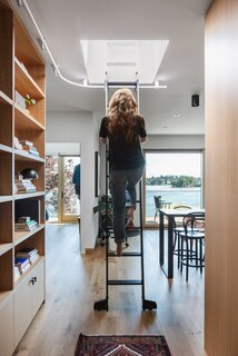 A rolling ladder gives Isabella access to the home's high-up shelves. It also cleverly slides along a railing that leads to a rooftop deck overlooking the waterway.