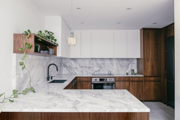 A mix of walnut veneer and solid walnut in the kitchen (like custom solid walnut handles) is paired with white quartzite countertop and backsplash.