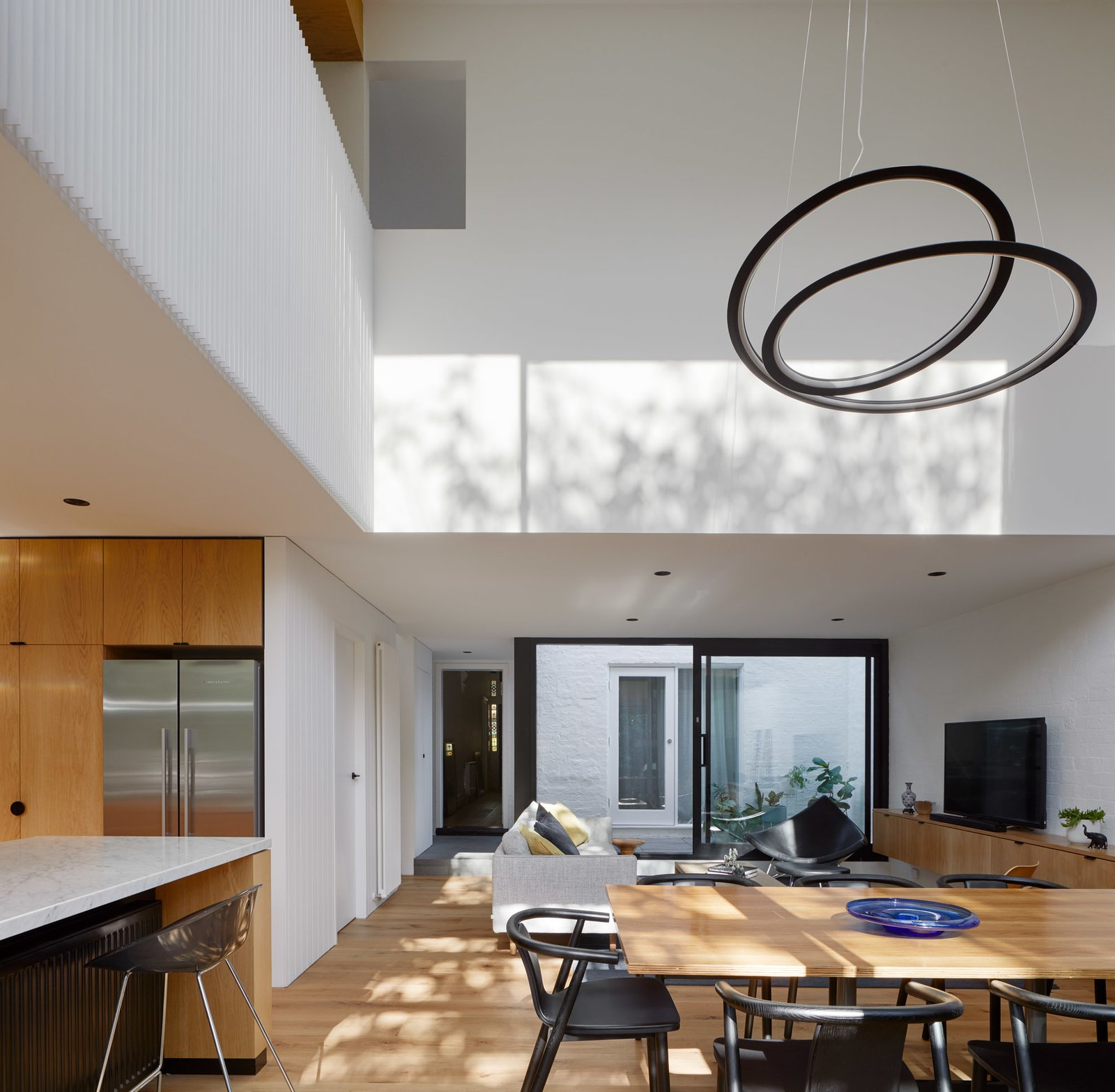 Dining Room, Medium Hardwood Floor, Ceiling Lighting, Pendant Lighting, Chair, and Table Void above Dining space  Photo 3 of 21 in Thanks to a Double-Height Dining Room, a Melbourne Home Basks in Sunshine and Courtyard Views from South Yarra Void House