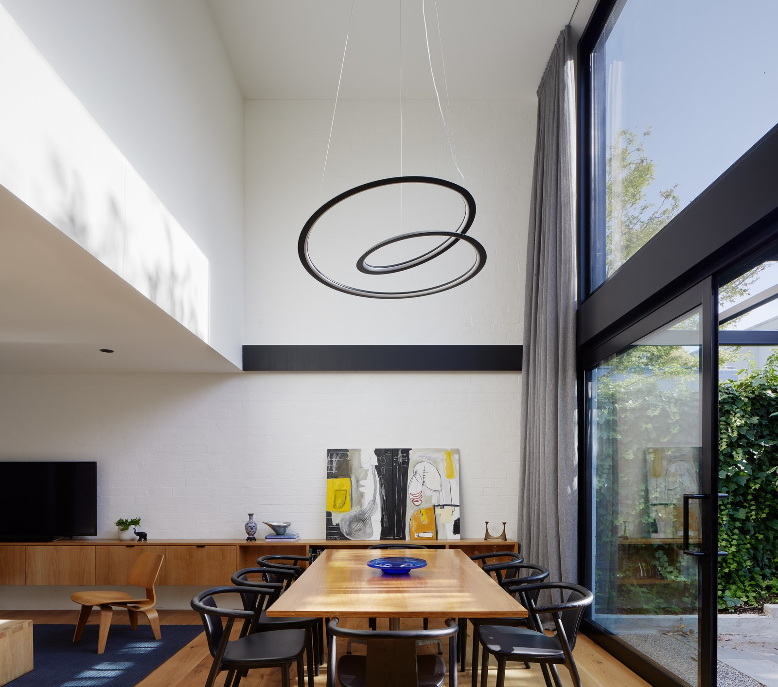 Dining Room, Chair, Table, Pendant Lighting, Medium Hardwood Floor, Shelves, Storage, and Ceiling Lighting Void above Dining space  Photo 2 of 21 in Thanks to a Double-Height Dining Room, a Melbourne Home Basks in Sunshine and Courtyard Views from South Yarra Void House