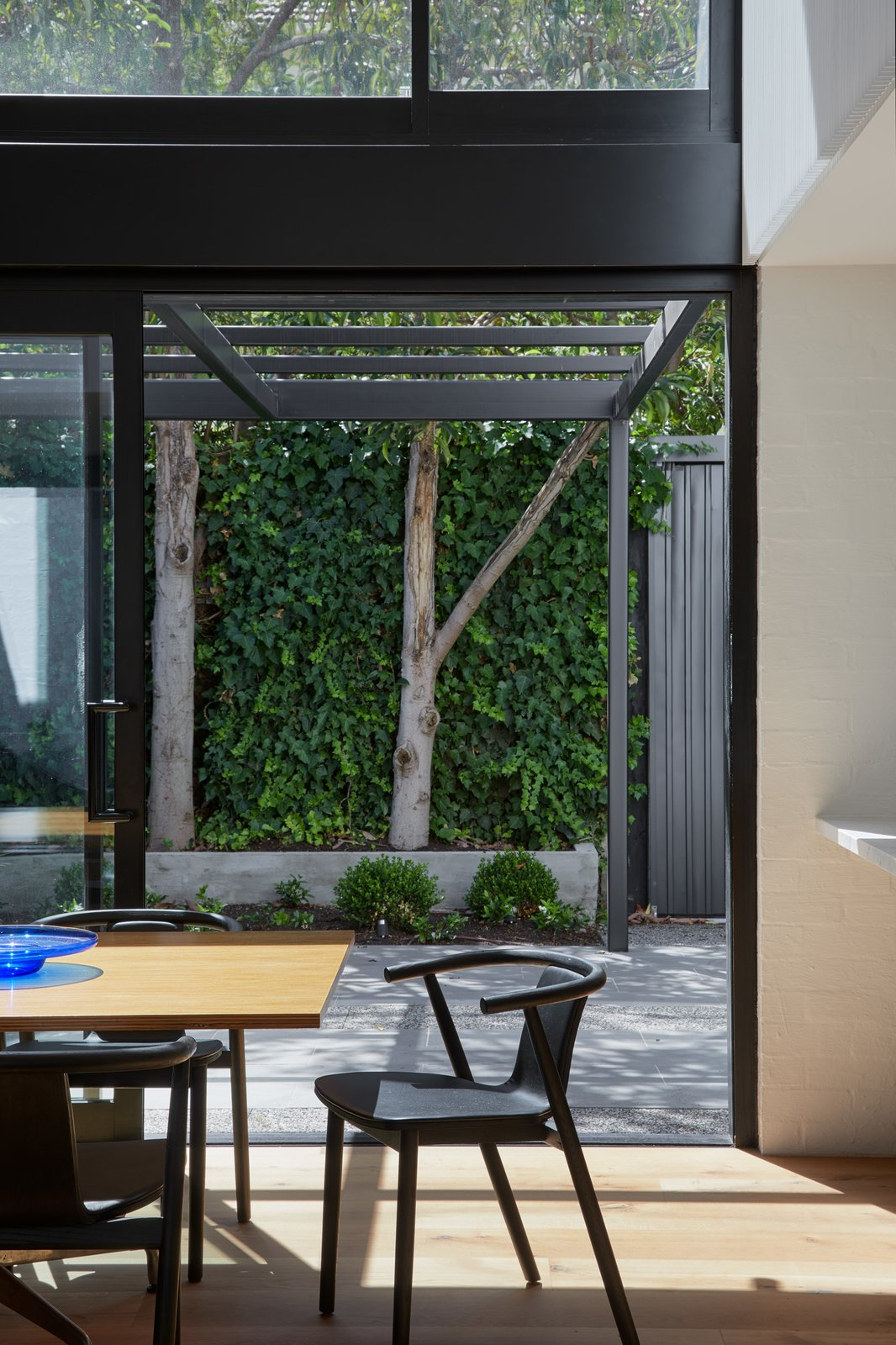 Dining Room, Chair, Light Hardwood Floor, and Table Dining space thru to rear garden  Photo 6 of 21 in Thanks to a Double-Height Dining Room, a Melbourne Home Basks in Sunshine and Courtyard Views from South Yarra Void House
