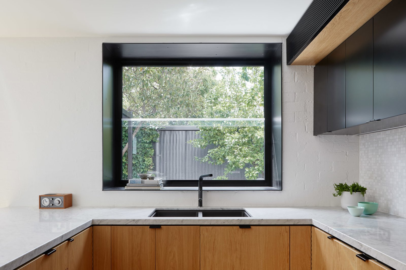 Kitchen, Glass Tile Backsplashe, Undermount Sink, Range Hood, Wood Cabinet, Marble Counter, Mosaic Tile Backsplashe, Dishwasher, and Light Hardwood Floor Kitchen box-bay window  Photo 9 of 21 in Thanks to a Double-Height Dining Room, a Melbourne Home Basks in Sunshine and Courtyard Views from South Yarra Void House