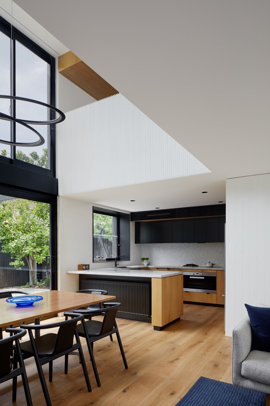 Dining Room, Chair, Table, Recessed Lighting, Light Hardwood Floor, Pendant Lighting, and Ceiling Lighting Void above Dining space  Photo 7 of 21 in Thanks to a Double-Height Dining Room, a Melbourne Home Basks in Sunshine and Courtyard Views from South Yarra Void House