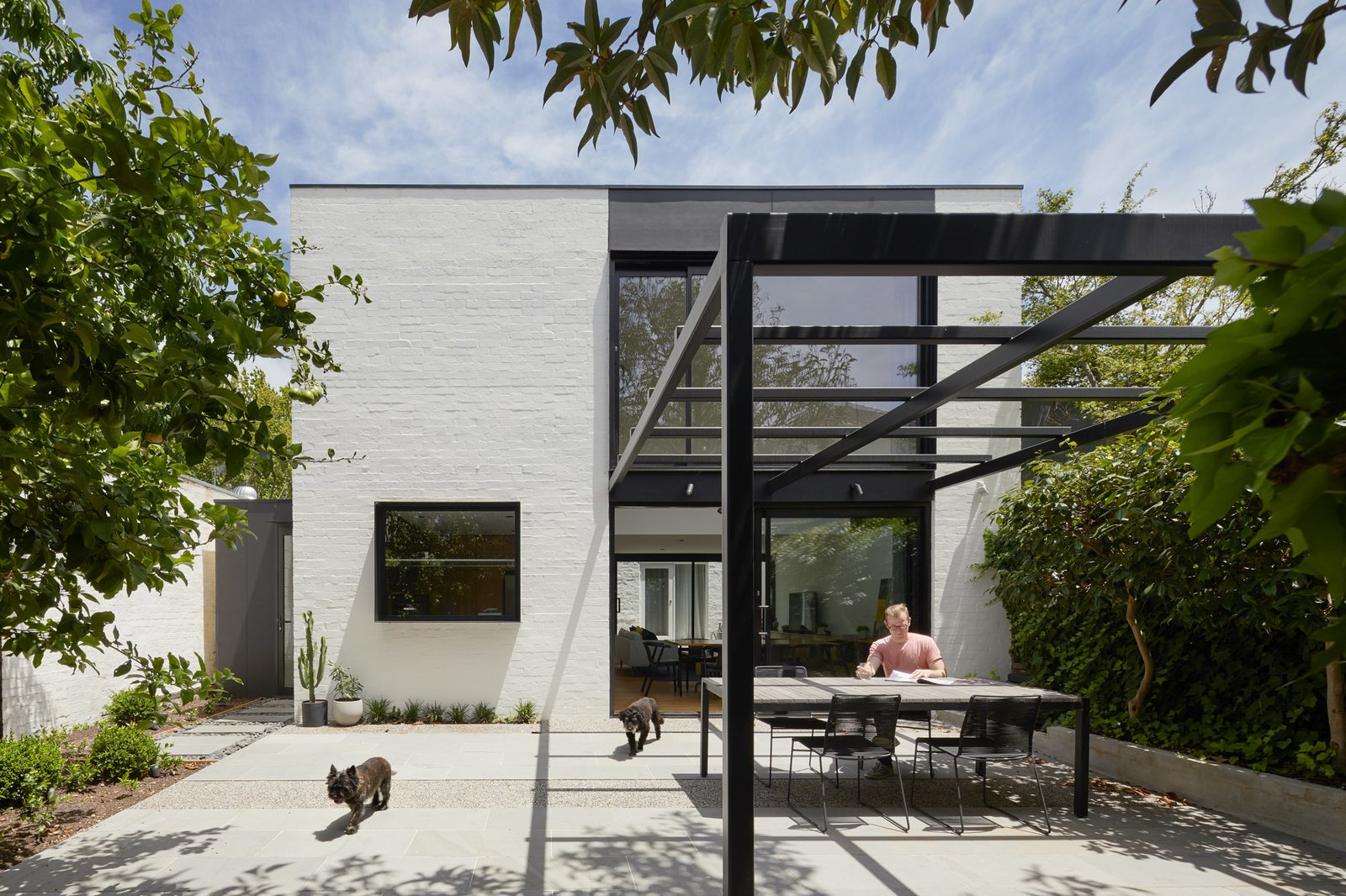 Outdoor, Back Yard, Raised Planters, Trees, Hardscapes, Metal Patio, Porch, Deck, and Shrubs rear outdoor space  Photo 17 of 21 in Thanks to a Double-Height Dining Room, a Melbourne Home Basks in Sunshine and Courtyard Views from South Yarra Void House