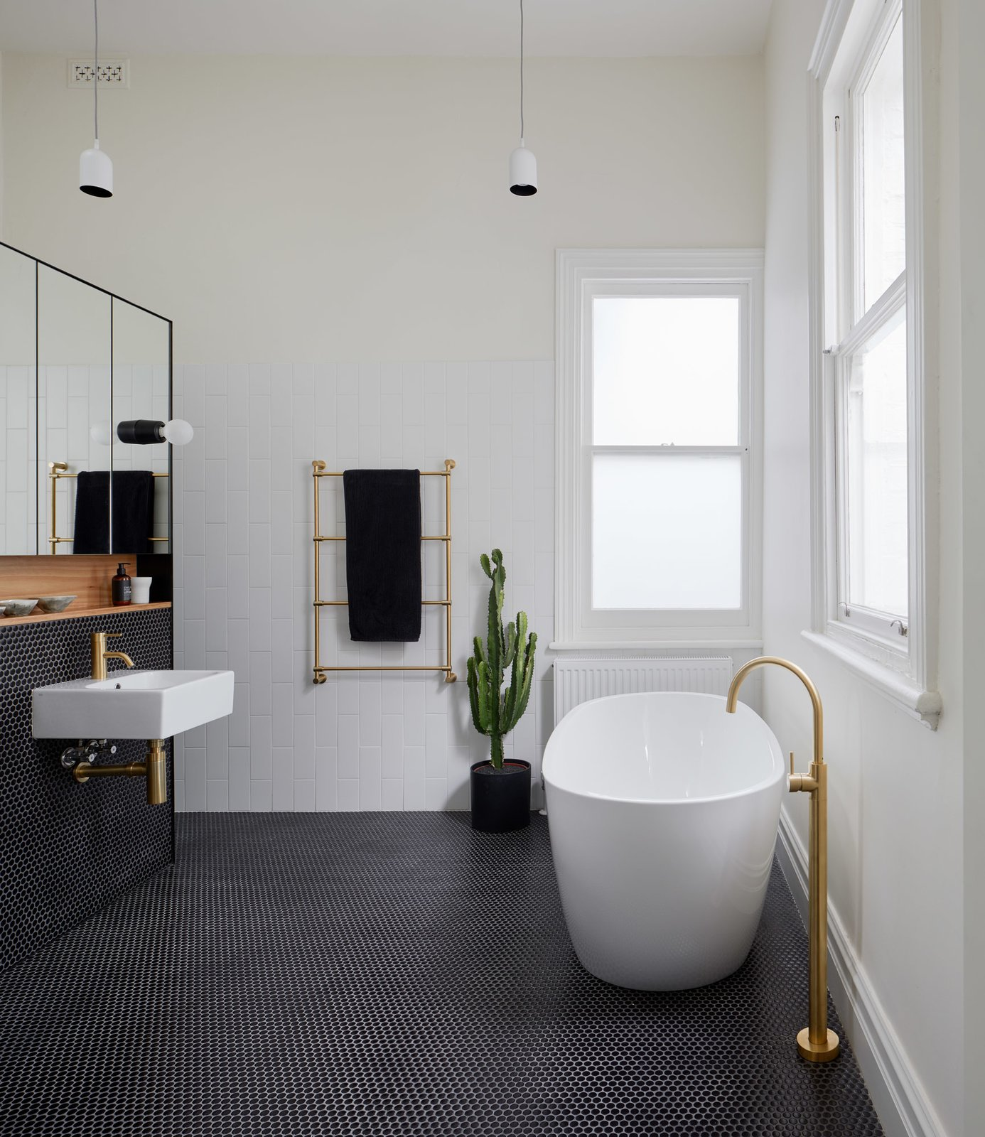 Bath Room, Wood Counter, Pendant Lighting, Wall Mount Sink, Ceramic Tile Wall, Ceramic Tile Floor, and Freestanding Tub Ensuite  Photo 15 of 21 in Thanks to a Double-Height Dining Room, a Melbourne Home Basks in Sunshine and Courtyard Views from South Yarra Void House