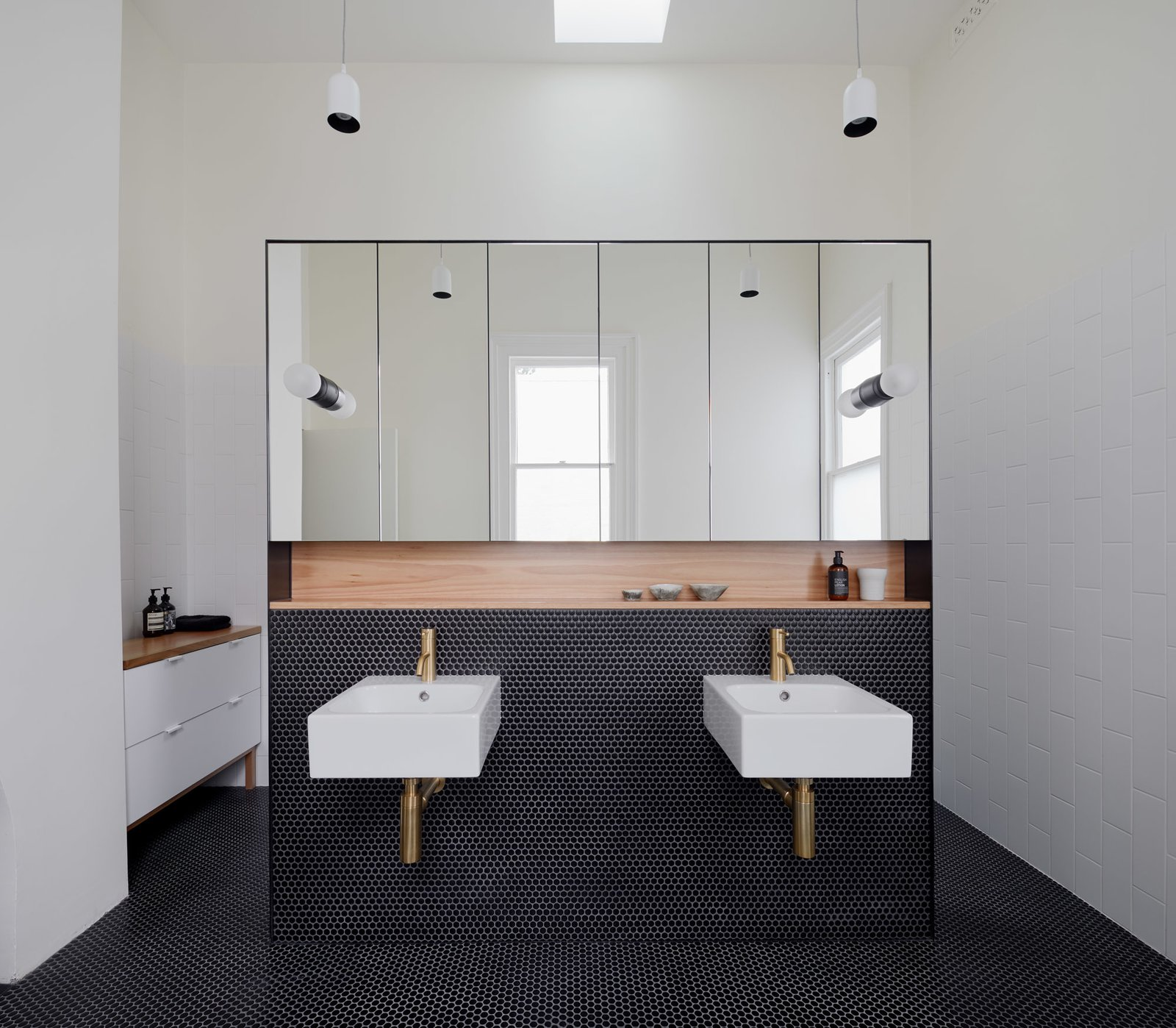 Bath Room, Ceramic Tile Floor, Wall Mount Sink, Wood Counter, Subway Tile Wall, and Pendant Lighting Ensuite vanity wall  Photo 13 of 21 in Thanks to a Double-Height Dining Room, a Melbourne Home Basks in Sunshine and Courtyard Views from South Yarra Void House