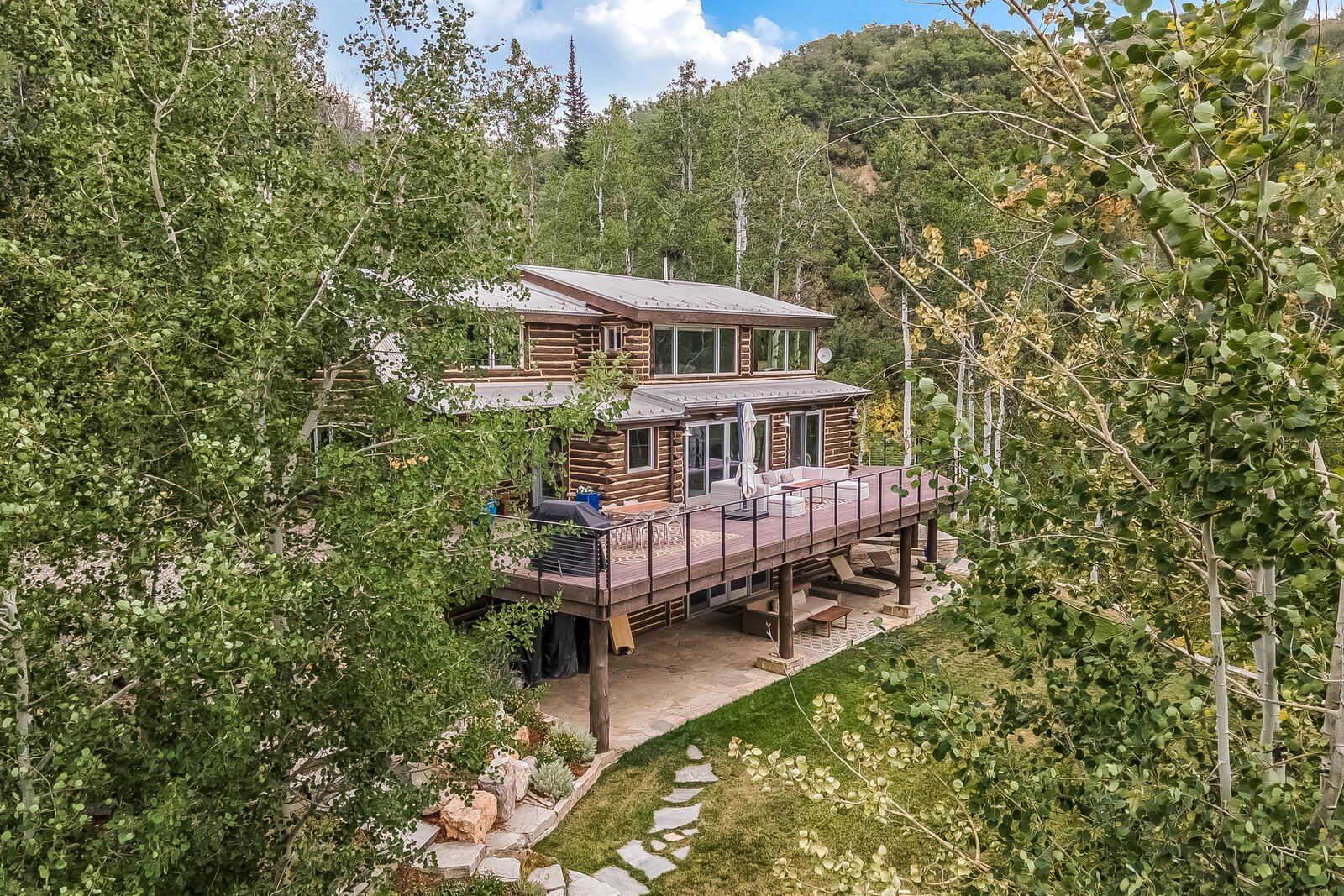 Back of home that overlooks east side of aspen grove.  Photo 1 of 16 in An Updated Log Cabin–Style Home in Colorado Seeks $2.4M