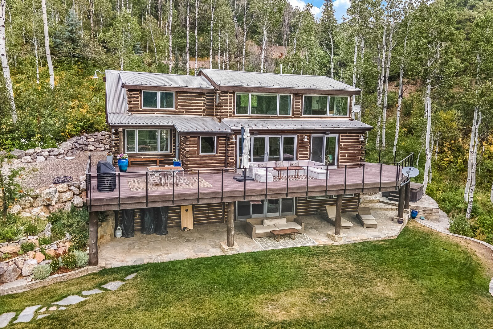 Another view of the back of the home featuring the large, wrap-around deck located on the first floor.  Photo 13 of 16 in An Updated Log Cabin–Style Home in Colorado Seeks $2.4M