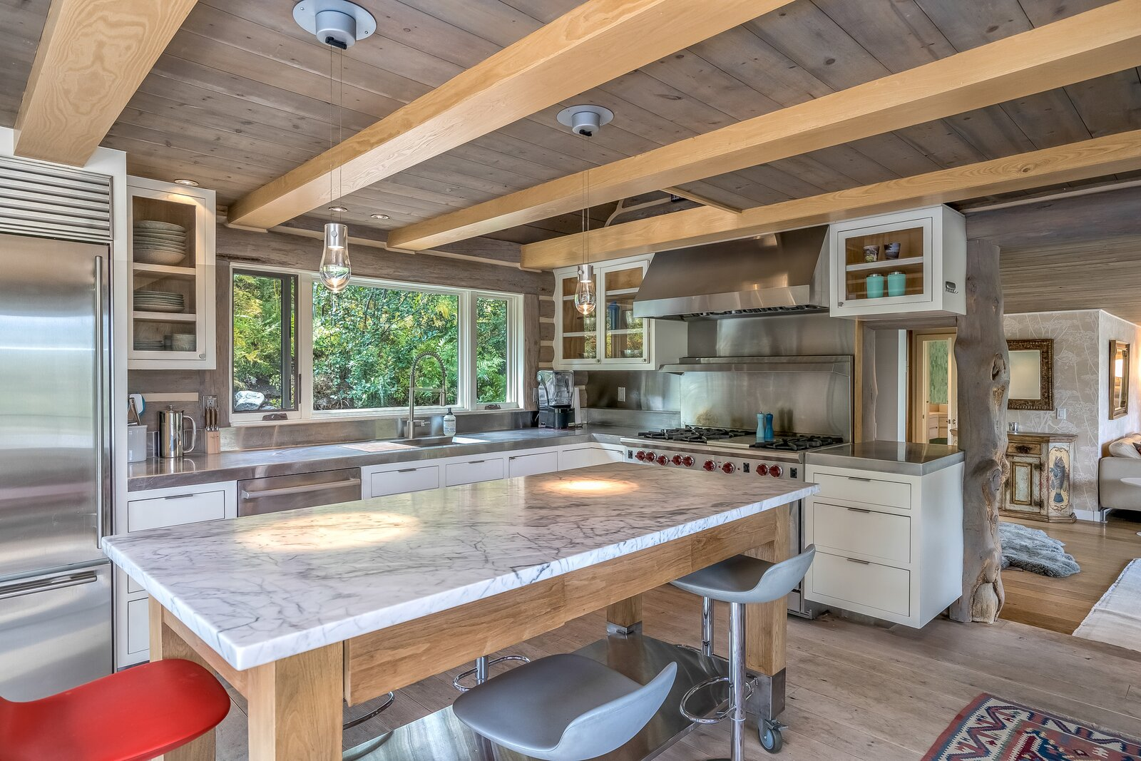 The updated kitchen features high-end, stainless steel countertops appliances, and finishes with glass cabinets and kitchen island. Contrasting exposed  beam ceiling visually opens up space.  Photo 4 of 16 in An Updated Log Cabin–Style Home in Colorado Seeks $2.4M