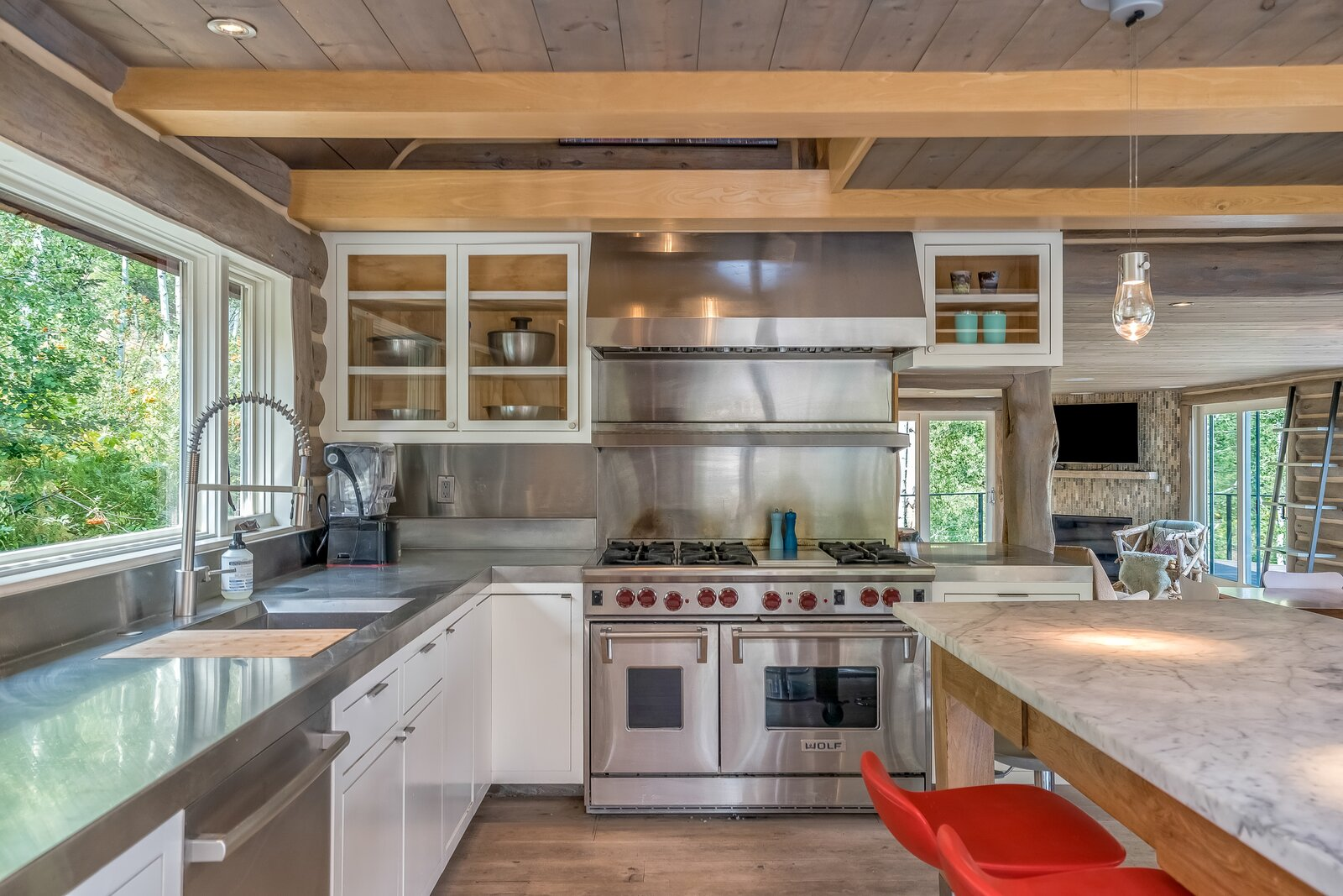 A close-up of the kitchen displaying the drop-in sink, pull-down spray faucet, and the updated gas oven with range hood.  Photo 5 of 16 in An Updated Log Cabin–Style Home in Colorado Seeks $2.4M