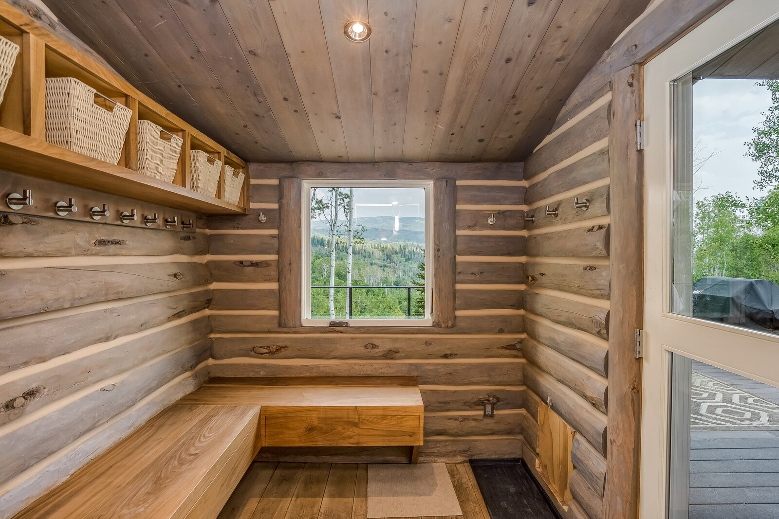 Mudroom offers exposed, shelf storage and stainless steel hooks with picture window overlooking aspen grove.  Photo 16 of 16 in An Updated Log Cabin–Style Home in Colorado Seeks $2.4M