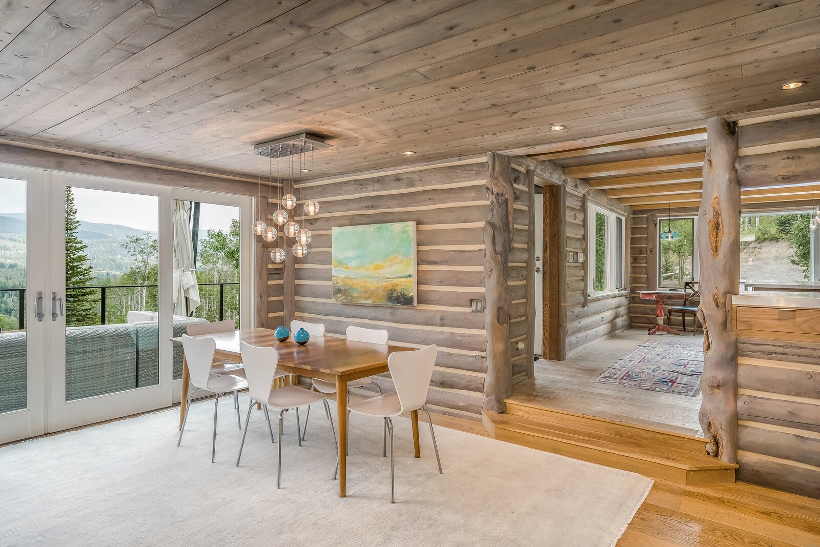 Dining area features pendant and recessed lighting.  Photo 6 of 16 in An Updated Log Cabin–Style Home in Colorado Seeks $2.4M