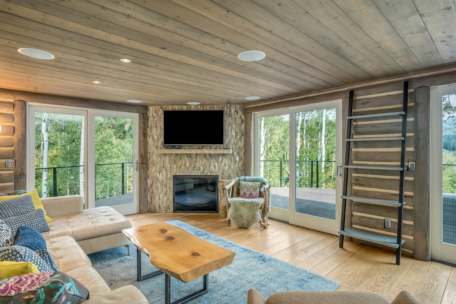 A close-up of the living area displaying the gas fireplace.  Photo 2 of 16 in An Updated Log Cabin–Style Home in Colorado Seeks $2.4M