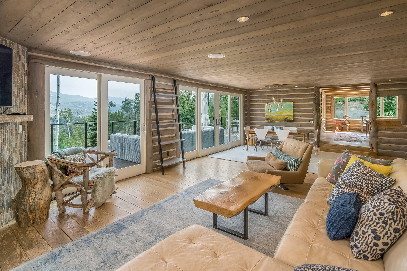 Another view of the living room offers a glimpse into the kitchen.  Photo 3 of 16 in An Updated Log Cabin–Style Home in Colorado Seeks $2.4M
