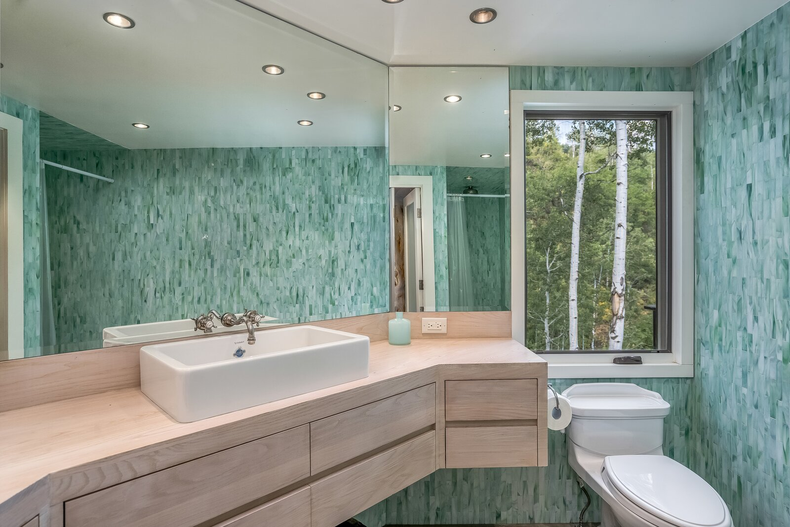 Bathroom features pale wood countertops to align with exterior and interior.  Photo 10 of 16 in An Updated Log Cabin–Style Home in Colorado Seeks $2.4M