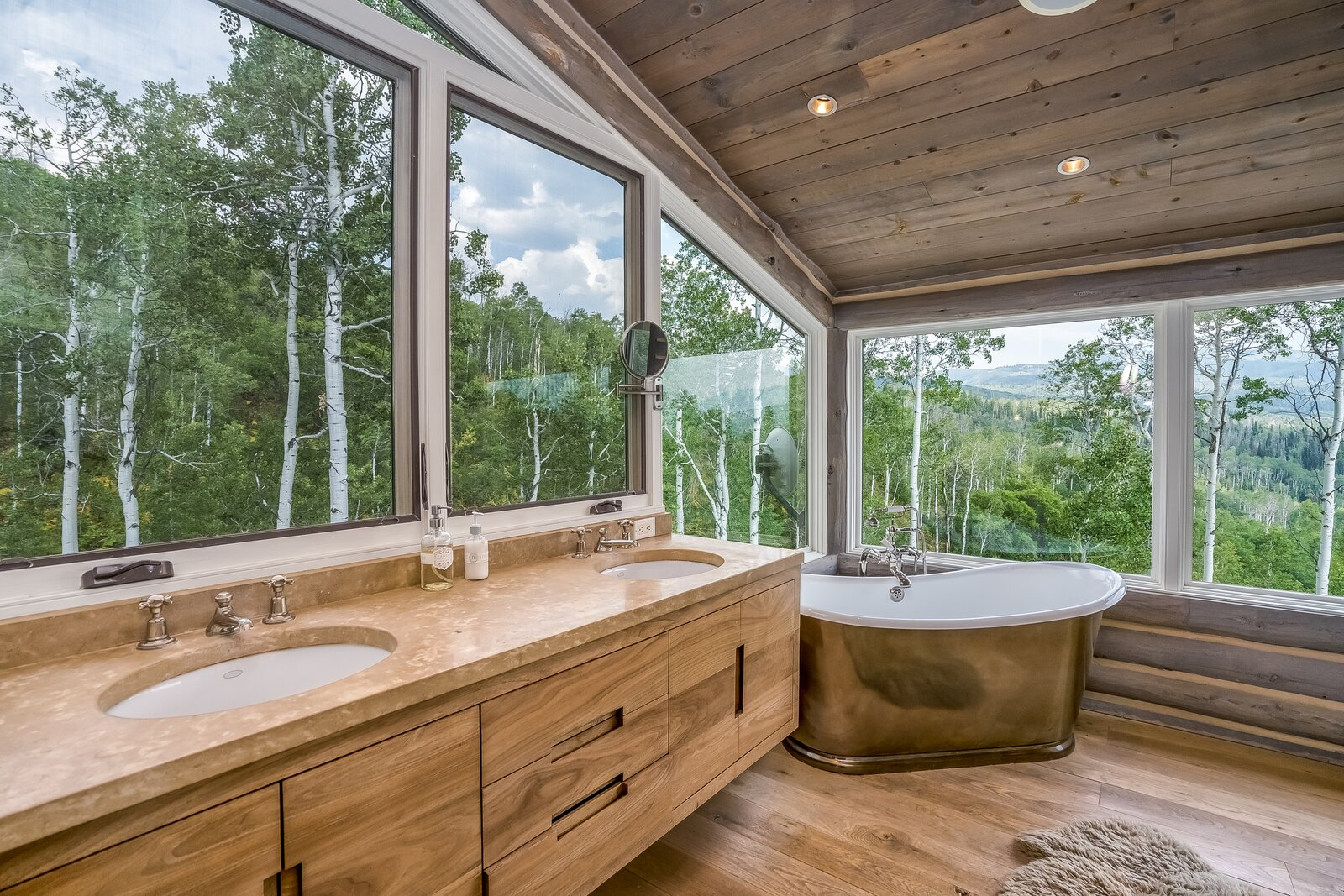 Bath Room, Stone Counter, Freestanding Tub, Medium Hardwood Floor, Drop In Sink, and Recessed Lighting The bathroom located just behind the sleeping space features picture windows that open up views to aspen tree grove.  Photo 8 of 16 in An Updated Log Cabin–Style Home in Colorado Seeks $2.4M