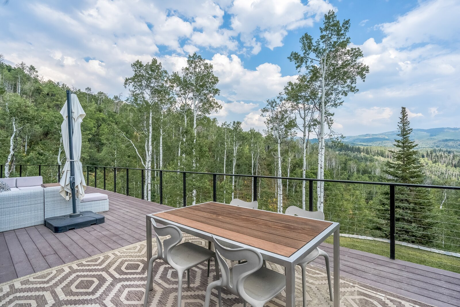 Outdoor, Woodland, Large Patio, Porch, Deck, Back Yard, Decking Patio, Porch, Deck, and Trees View from wrap-around deck on first floor of property.  Photo 15 of 16 in An Updated Log Cabin–Style Home in Colorado Seeks $2.4M