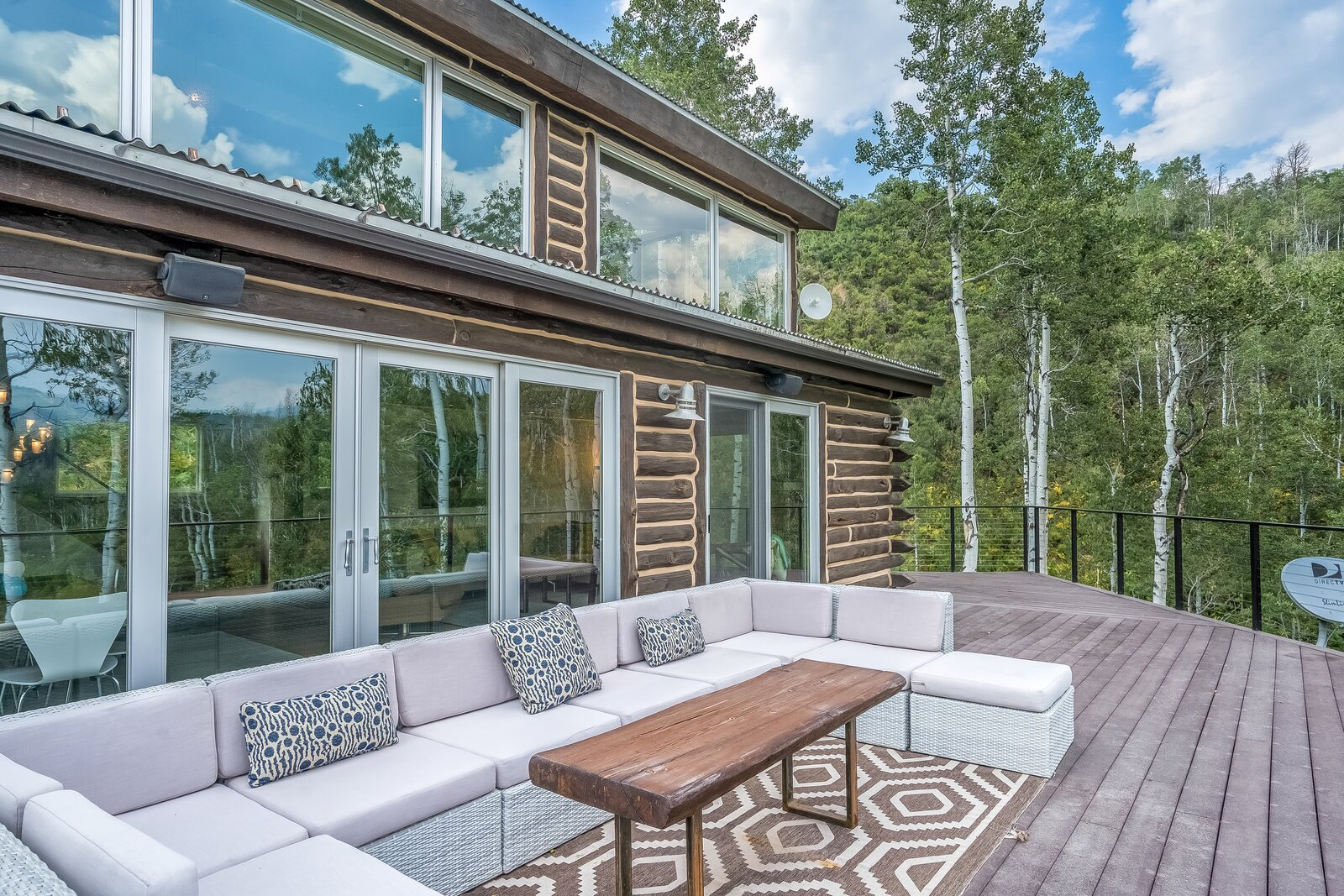 Outdoor, Back Yard, Trees, Large Patio, Porch, Deck, and Decking Patio, Porch, Deck Large wrap-around deck area provides ample room for comfortable, outdoor furniture.  Photo 14 of 16 in An Updated Log Cabin–Style Home in Colorado Seeks $2.4M