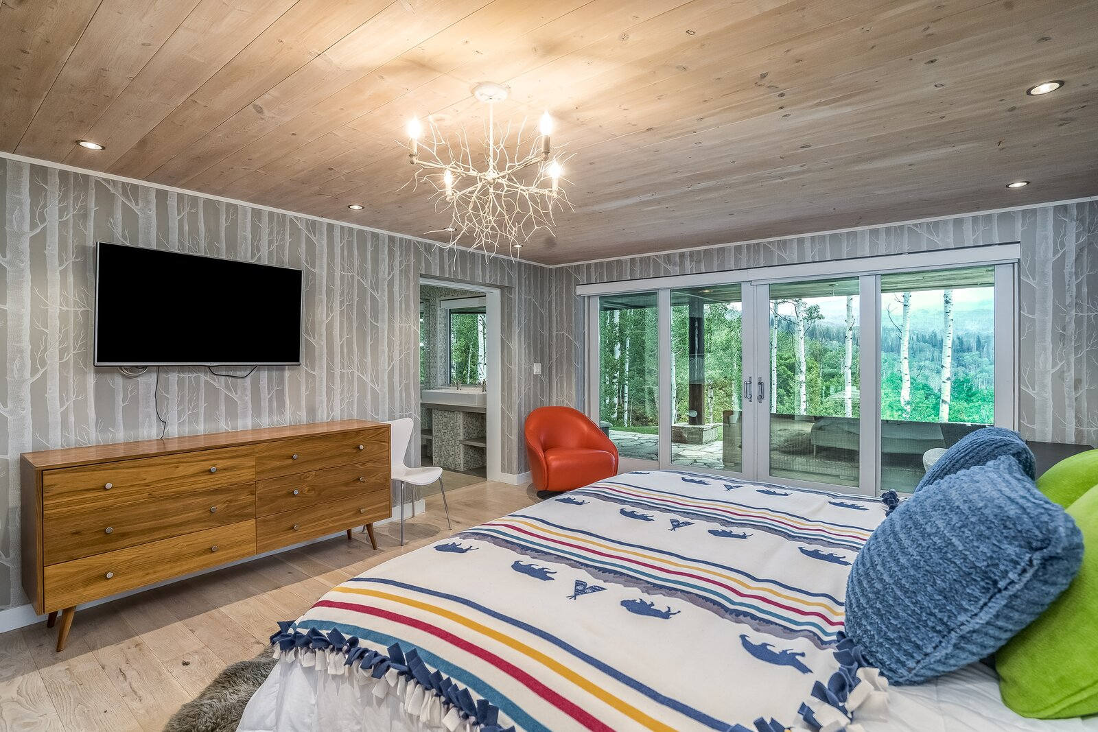 Bedroom, Bed, Light Hardwood Floor, and Chair Bedroom on ground floor featuring sliding glass doors and full bathroom.  Photo 11 of 16 in An Updated Log Cabin–Style Home in Colorado Seeks $2.4M