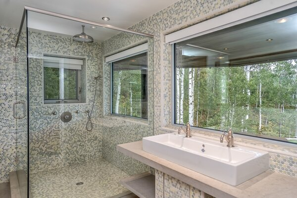 Enclosed shower is attached to picture windows for open views of the surrounding forest area.