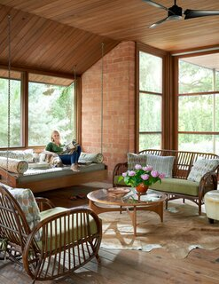 Brenda and Ruby sit comfortably on the swinging daybed, located in their screened-in porch. The wicker furniture, found in Maine, is over 100 years old.