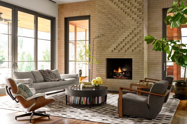 In the Bogarts' living room, a brick fireplace inspired by Josef Albers commands attention and changes with the daylight. The artist made the bowl filled with yellow flowers in college.