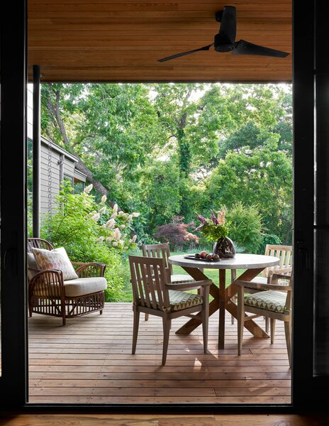 The intimate back patio features an antique wicker chair from Maine along with a zinc table from Arteriors and outdoor dining chairs from David Sutherland.