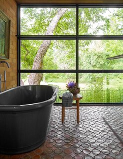 The serene principal bathroom features floor-to-ceiling windows and a deep soaking tub where the artist unwinds every evening.