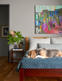 The Bogarts' beagle, Ranger, lounging on their bed. The painting, All is Well, is an abstract from Brenda's early days as a painter.