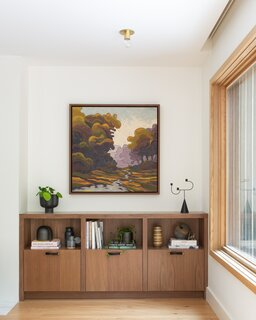 Baker drew unexpected colors from this abstract landscape painting. Shades of hunter green and pale lavenders pair well with the range of neutral tones, including the walnut wood tones of the floating cabinetry