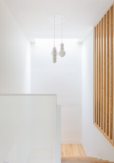The sleek stairwell features a monotone white color palette. A range of textures comes into play with the milk glass pendant light and the wall of powder-coated steel mesh.