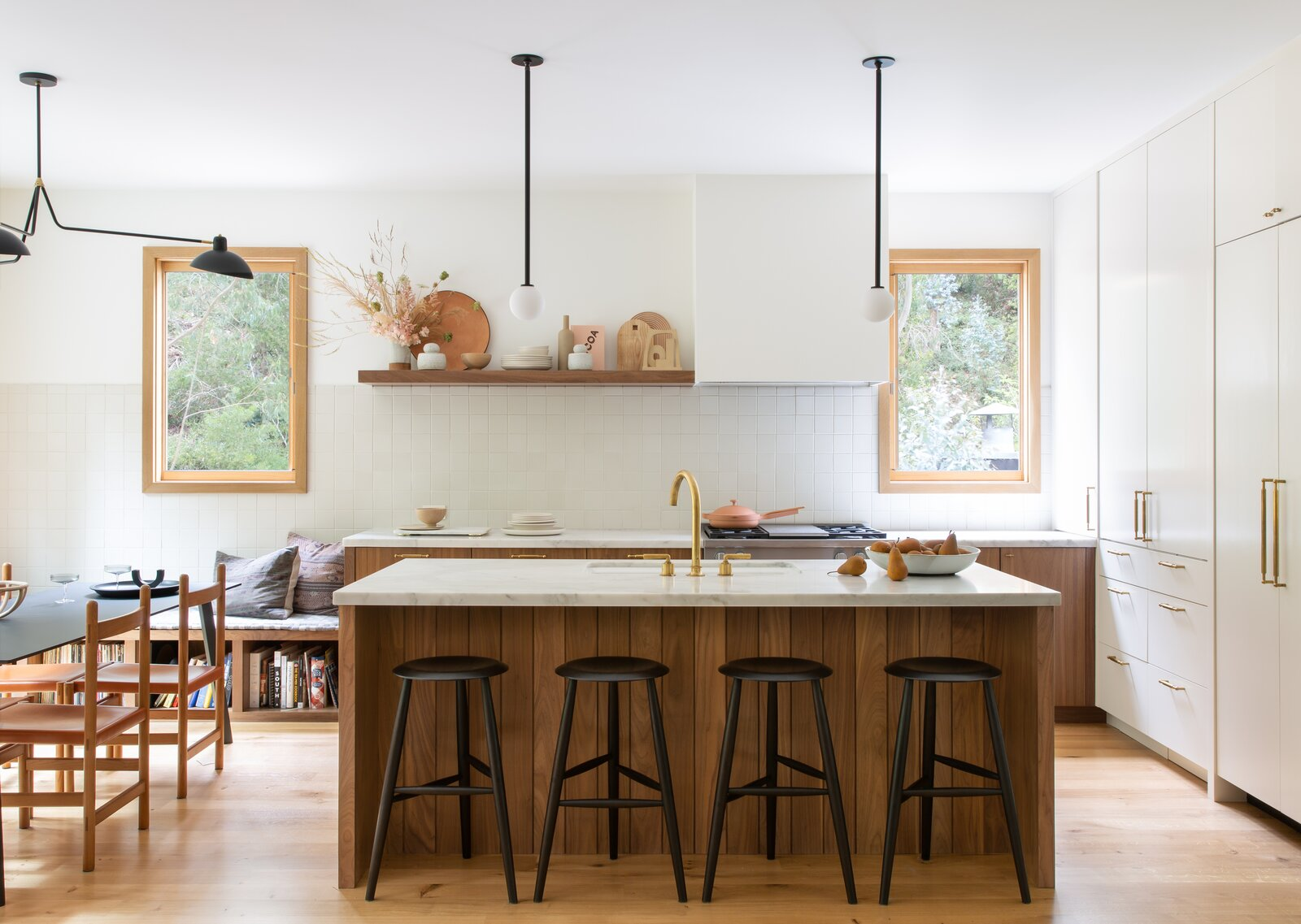 Kitchen, Light Hardwood Floor, Ceramic Tile Backsplashe, Pendant Lighting, Cooktops, Drop In Sink, White Cabinet, Subway Tile Backsplashe, and Marble Counter The kitchen tiles are by Heath Ceramics with barstools by March SF and pendant lights by Allied Maker.  Photo 6 of 14 in This Colorful House in San Francisco May Be Boxy, but It's Anything but Square