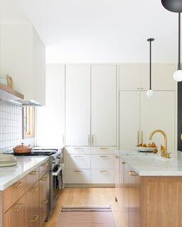 The kitchen is a central gathering place for the Baker family. The custom cabinetry was painted a light white color to make it feel a part of the wall.