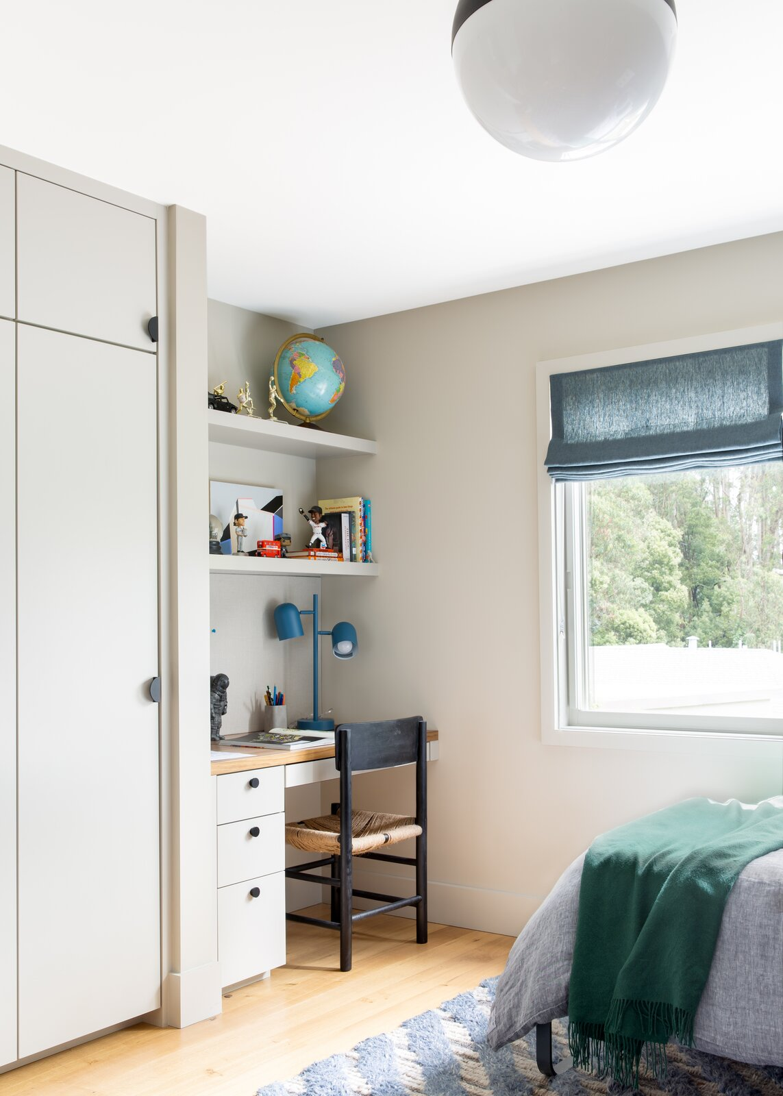 Kids Room, Bedroom Room Type, Shelves, Chair, Light Hardwood Floor, Pre-Teen Age, Lamps, and Rug Floor Everett's built-in desk features trophies, a globe, and a chair by Urban Outfitters.  Photo 11 of 14 in This Colorful House in San Francisco May Be Boxy, but It's Anything but Square