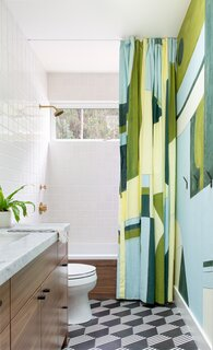 The colorful Porter Teleo wallpaper and custom, commissioned shower curtain in the kid's bathroom is offset by a funky white and charcoal tiled floor.