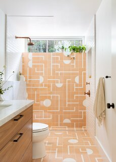 A geometric, peach-colored tile in the master bathroom adds a joyful jolt to the home. The walnut cabinetry is an ode to the home's mid-century roots.