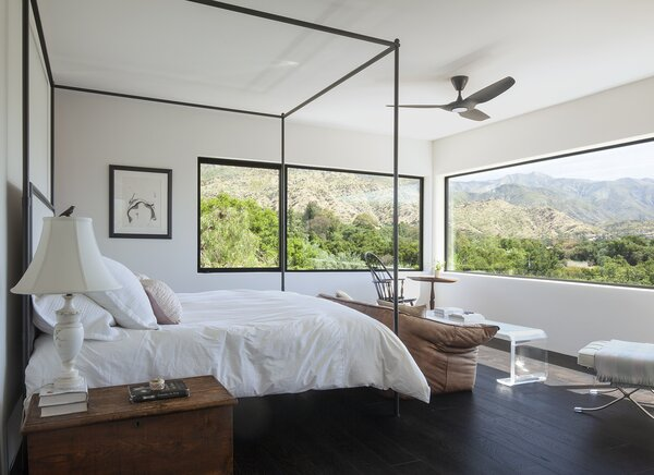 The couple's bedroom overlooks the surrounding Ojai landscape. To the left of the windows is a coveted drawing by Guy Dill.