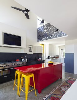Also designed by Roy McMakin is the glossy red island in the family's double-height kitchen.