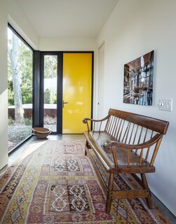 The home's sunny vestibule features a vibrant yellow door and a photo by William Bailey.