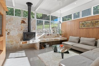 A view of the cozy lounge room, with its fireplace, sandstone rock wall, and windows overlooking the lush surroundings.